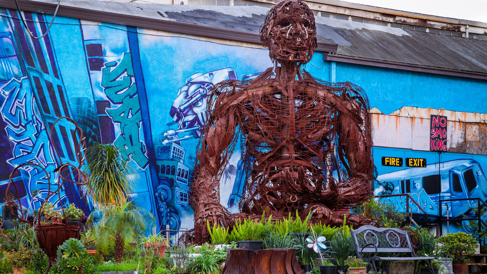 Oxidized metal sculpture of a giant-sized torso in front of a colorgully painted wall lined with potted plants.
