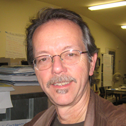 Brian Beveridge smiles, wearing wire-framed glasses and a brown jacket.