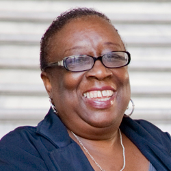 Head shot of Ms. Gordon in dark-framed glasses and blue blazer, smiling at the camera.