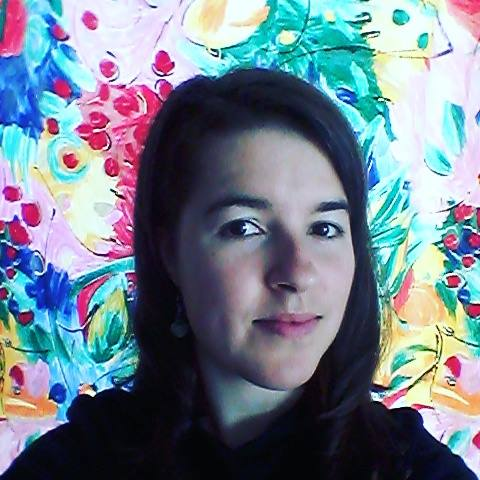 Close-up of Meg loking straight at the camera in a dark shirt against a multi-color floral background.