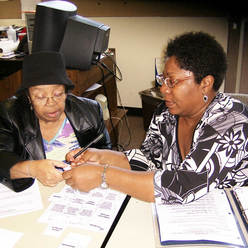 Volunteer Cassandra Martin trains a senior neighbor about air quality as they pour over several notebooks.