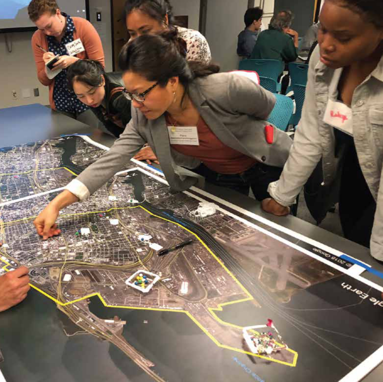 West Okland residents and air quality experts stand around a large table-top map, while a woman with dark hair and glasses points to the center of it.