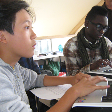 Young male student sits at a laptop in the WOEIP office.