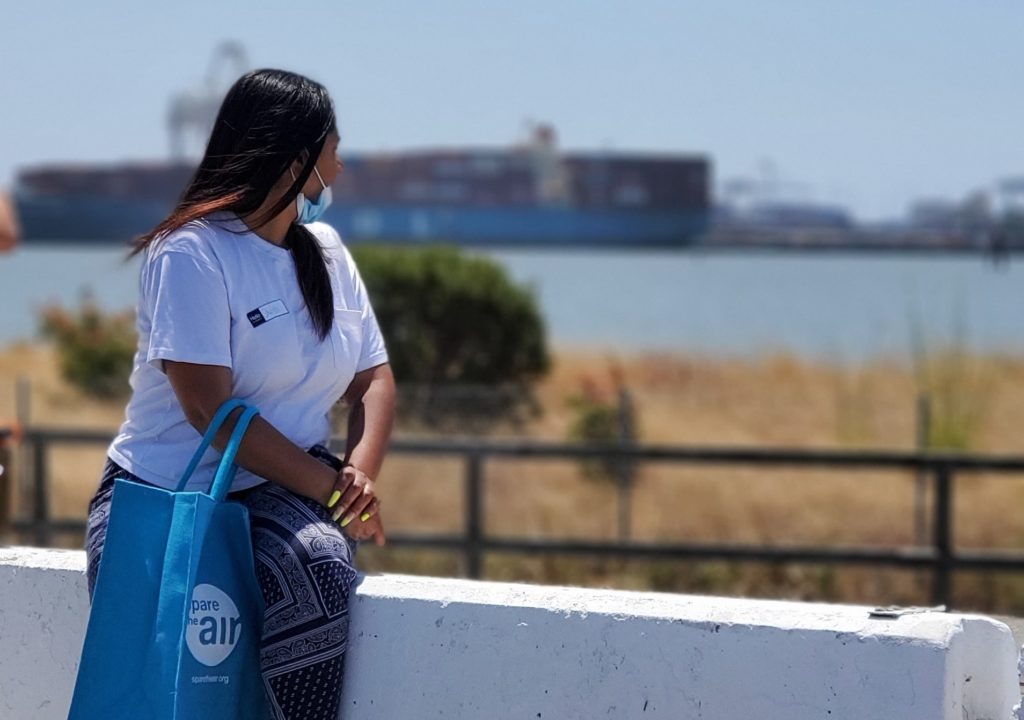 A woman with long brown hair sits on a concrete barrier with her head turned away from the camera, looking out over a grassy area to waters of Oakland's Outer Harbor. Giant cargo containers can be seen aross harbor in the distance.